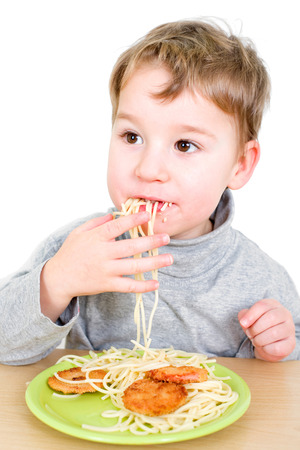 Toddler eating spaghetti and cutlet with his fingers