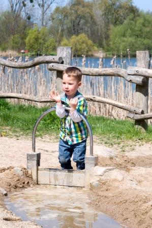 Jongetje spelen met water op het strand