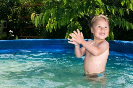 Little happy boy playing in poolKleiner fröhlicher  Junge spielt im Pool Banco de Imagens