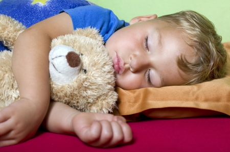naptime: sleeping boy with teddy bear in his arms