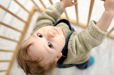 playpen: Little boy in playpen looks into the camera Stock Photo
