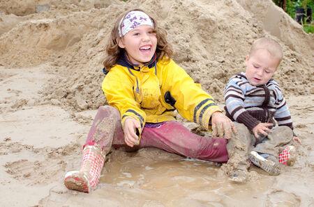 gelukkig broers en zussen spelen in de modder Stockfoto