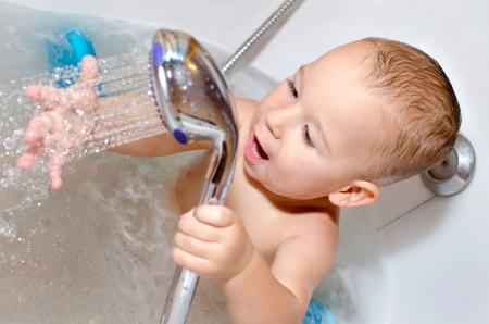 Kleiner Junge spielt mit Wasser in der Badewanne Standard-Bild - 25291213