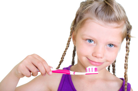 Girl with long braids brushes her teeth photo