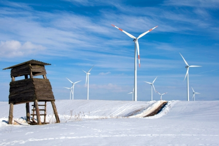 Wind turbines in the snow behind a dilapidated hunting seat