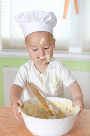 Little boy with bowl of dough photo