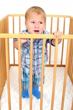 Kleine böse Junge ist in Laufstall zu weinen Standard-Bild - 25391565