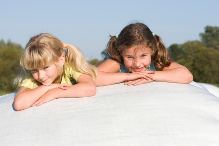 countrylife: two girls relax on straw bales Stock Photo