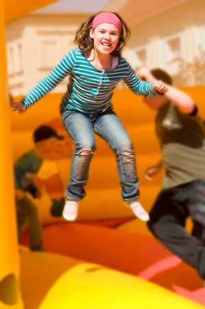 Girl jumping on the bouncy castle photo