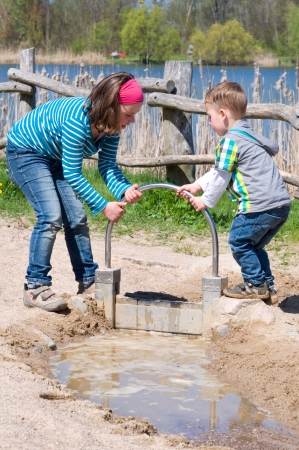 Jonge geitjes spelen op het speelgrond met water