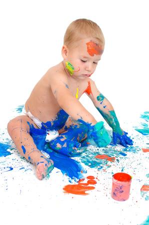 Little boy paints with finger
