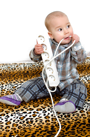 small child plays with power plug and takes power cord into the mouth. photo