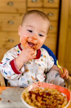 Kleiner Junge im Pyjama essen Pasta mit Tomatensauce mit den Fingern Standard-Bild - 26751614