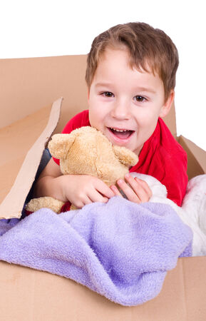 removals: little boy sitting with stuffed animal in a cardboard box and laughs Stock Photo