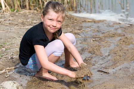 Lächelndes Mädchen spielt mit Wasser am Strand Standard-Bild - 27264477