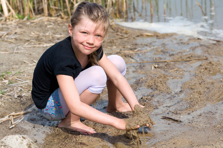 puddle: smiling girl plays with water at the beach
