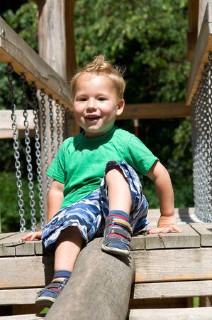 romp: little boy sits on the climb