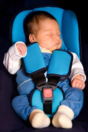 asiento coche: Niño en un asiento de coche con el cinturón de seguridad Foto de archivo