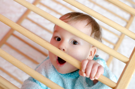 playpen: little astonished boy in playpen