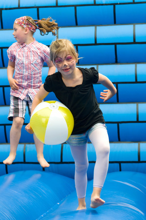Girl on a blue bouncy castle photo