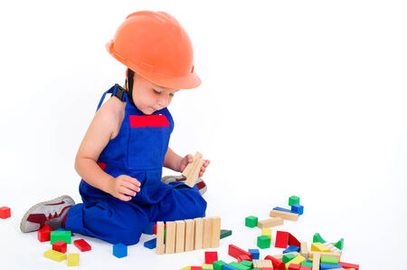 little boy as a construction worker building with colorful blocks photo