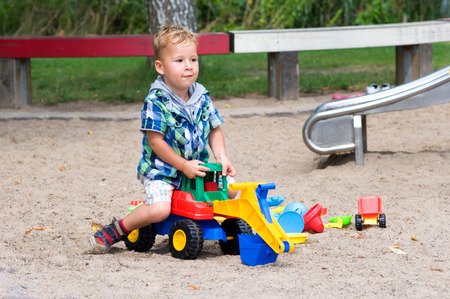 bagger: little boy playing with digger in the sand