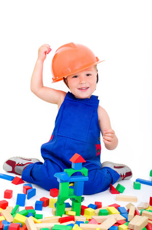 little boy with a hardhat plays with colorful bricks photo
