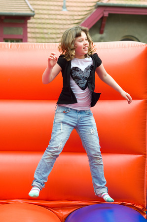 young girl jumping on a red bouncy castle photo