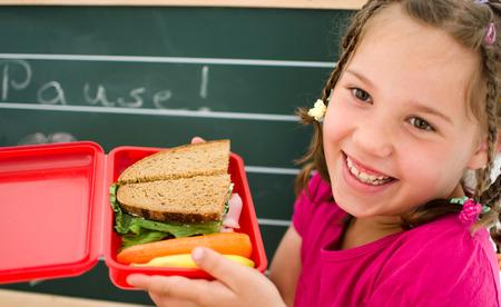 niño escuela: niña feliz con merienda saludable