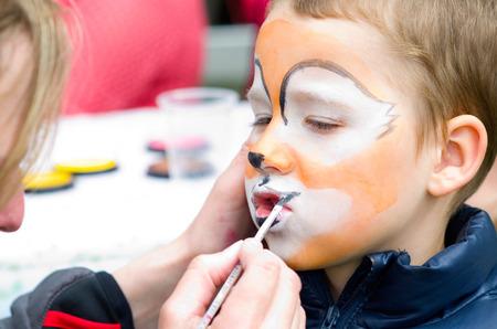 kleine jongen die make-up in het masker Stockfoto