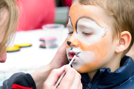 little boy applying makeup in the mask photo