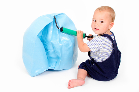 bloat: little boy playing with an air pump and an exercise ball