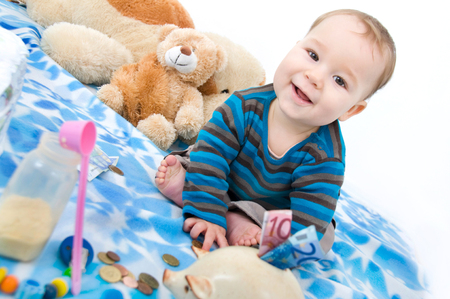 little boy on a baby blanket with money and baby utensils photo
