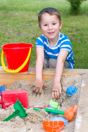jongetje spelen in de zandbak met zand speelgoed