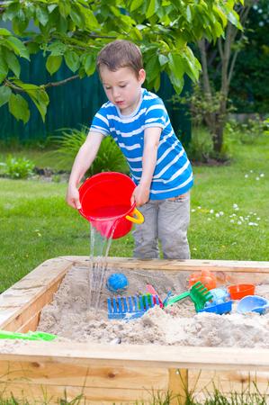 kleine jongen spelen met water in de zandbak Stockfoto
