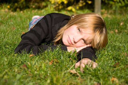 late summer: young girl lies on a lawn in late summer
