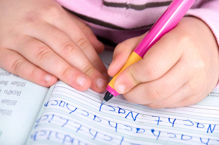 Childrens hands at the first writing exercises photo