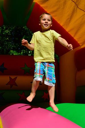 littly boy jumps at a baoncy castle photo