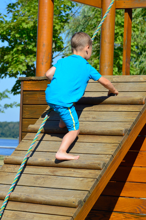 wall bars: little boy climbs on a wall bars Stock Photo