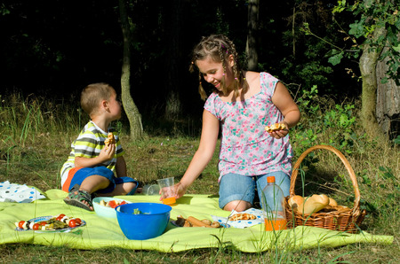 Kids eats a picnic with healthy food photo