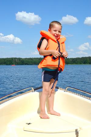 little boy standing on a boat in lifejacket