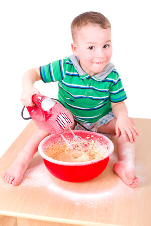 little boy cake mixes in a red bowl Stock Photo