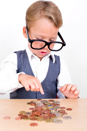 sparingly: little boy in a suit counts coins Stock Photo