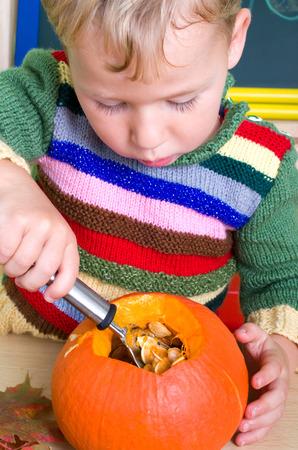 little boy carving on a pumpkin lantern Banco de Imagens