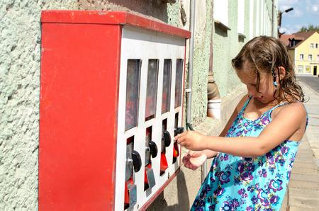 Kleines Mädchen in einem Automaten für Süßigkeiten und Spielzeug Standard-Bild - 32009723