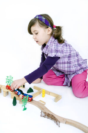 Little girl playing with a wooden train