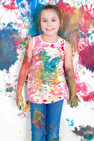 Meisje met de vinger verf op de muur Stockfoto