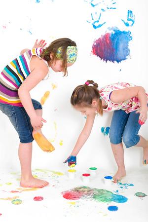 twee meisjes verf hun voeten met kleur Stockfoto