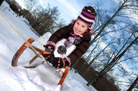 toboga: bambina con un toboga slitta di legno