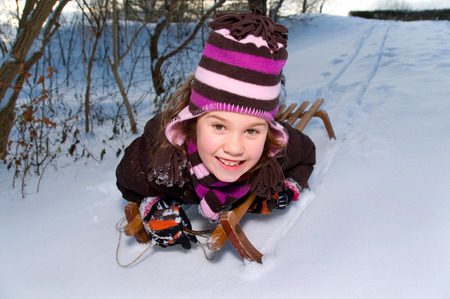 toboggan: little girl on a wooden toboggan sled down a mountain